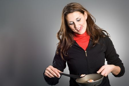 A beautiful young woman frying eggs in a pan. photo