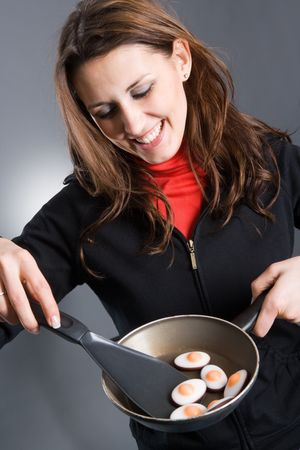 Smiling woman holding frying pan containing eggs and using spatula. Eggs are Candy-Eggs - sugar. photo