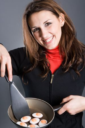 A beautiful woman frying eggs in a pan. Eggs are made of sugar. photo