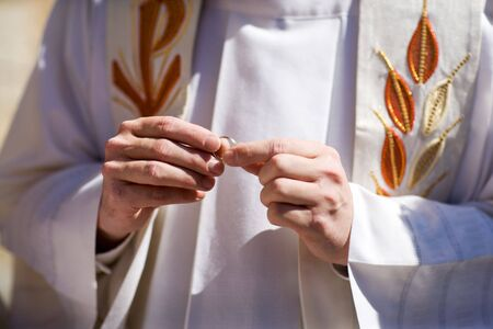 A closeup view of a priest or minister in a white robe and stole, holding wedding rings.