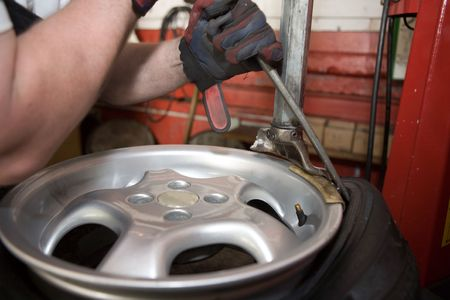 A mechanic removing a tire from a car wheel, in a workshop.