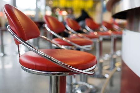 Line of red and chrome diner stools. Stock Photo