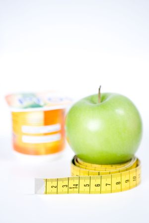 Tape measure coiled around apple with yogurt pot in background, dieting concept isolated on white background. photo