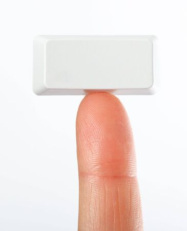 Just a small empty rectangular key from a computerkeyboad on fingertip, white background Stock Photo