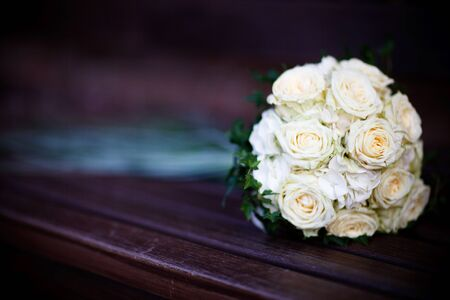 Just white roses as a bouquet, lying on dark ground. Shallow DOF.