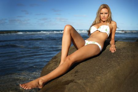blonde bikini: blonde bikini woman on rock at the beach Stock Photo