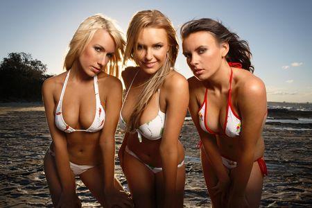 beach breast: three bikini models on rocky beach leaning toward camera