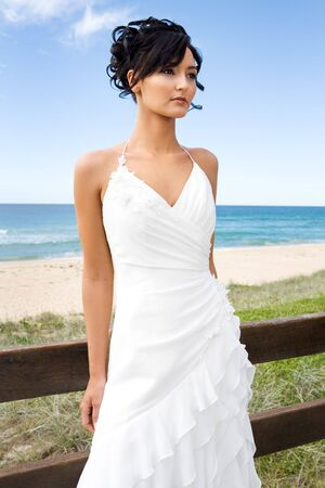 debutante: young brunette bride in wedding gown on beach