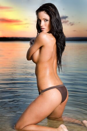 girl boobs: sexy brunette woman in water at sunset Stock Photo