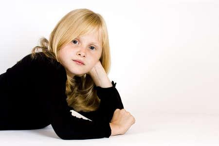isolated young blonde girl lying on floor