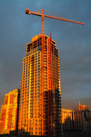 A new apartment tower block being constructed in downtown Vancouver, British Columbia, Canada. Crane and building in the evening cross light. photo