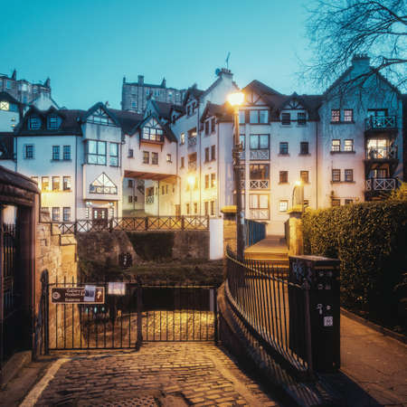 View on old houses and a street lit by yellow light from street lamps in Dean village and the bridge cross Leith river. In the evening, blue hour. New Town part of Edinburgh city, capital of Scotland,
