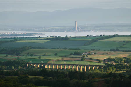 View of a rural Scottish landscape with a stone bridge, sea and mountains. Avon Viaduct, Linlithgow, Scotland