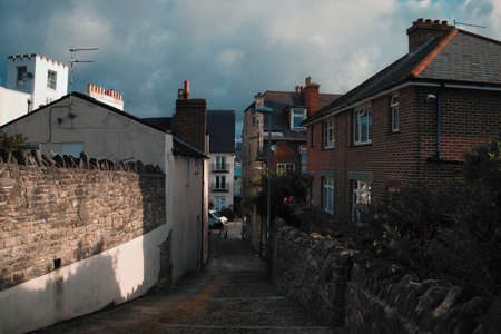 Narrow street of an English city with an old stone wall lit by bright sun. Swanage, United Kingdom
