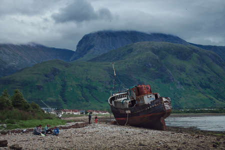 JULY 11, 2020. People rest on the shore of the sea bay near an old ship washed ashore at the end of the lockdown. At Fort William on the Highland coast of Scotland Stock Photo