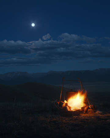 At night on a bonfire there is a bowler hat, a landscape against the background of mountains and the moon