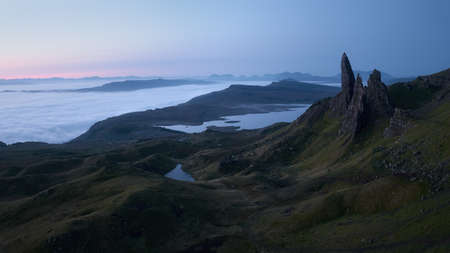 Atmospheric mysterious top view of the high sharp cliffs towering over the lakes and the sea covered with low clouds before dawn. The Old Man of Storr, The Isle of Skye, Scotland, UK.