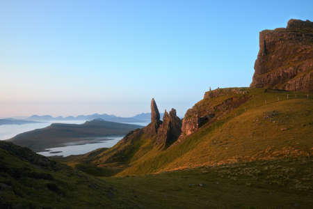 Sunny landscape with the high sharp cliffs towering over the lake and the sea in the morning and small figures of people. The Old Man of Storr, The Isle of Skye, Scotland, UK 版權商用圖片