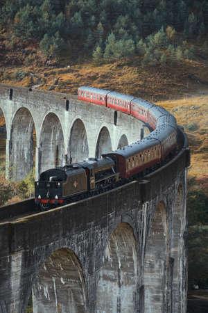 Old historical steam train riding on famous viaduct bridge. Travel and tourist destination in Europe. Glenfinnan Viaduct, Highlands, Scotland, United Kingdom 免版税图像