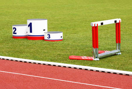 Track lanes with winners podium and hurdles on green grass