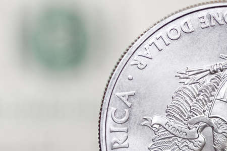 Silver shiny one dollar coin on a blurry background of dollar bill photo