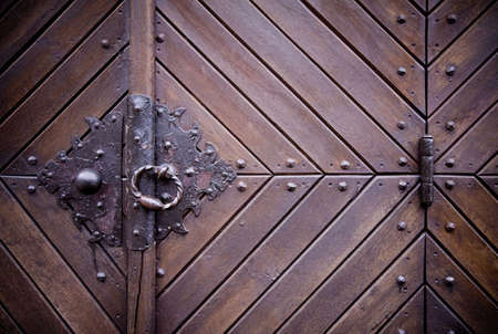 Steel medieval knocker on the old wooden historic door, hinge photo