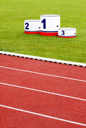 Track lanes with winners podium on green grass photo