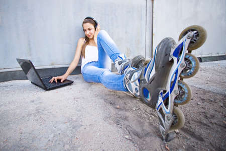 Young girl with laptop, headphones and roller shoes listening to the music photo