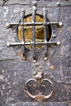 Steel medieval knocker on the old metal historic door with bars Stock Photo - 12445640
