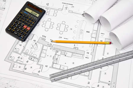 Calculator, scale ruler and pencil on architectural drawing blueprint