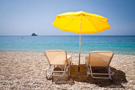 yellow umbrella: Sun loungers and parasol on the beach Stock Photo