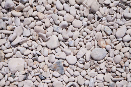 multiplicity: Background of bright, small stones on a stony beach