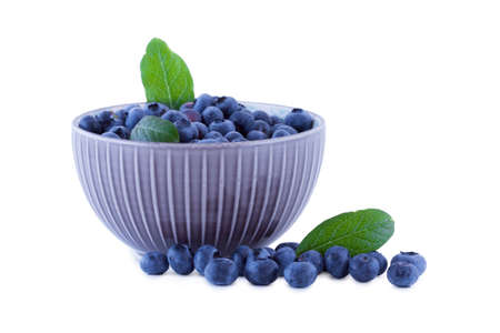 Blueberries in a porcelain bowl, fruits isolated on white background