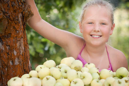 Nice young girl with stack of green fresh apples in the orchard