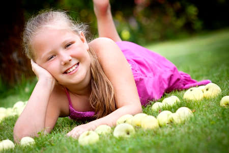 Nice young girl with stack of green fresh apples in the garden