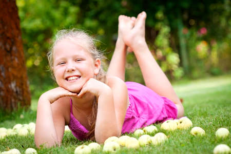 Cute young girl with stack of green fresh apples in the garden Imagens