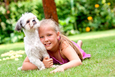 Cute young girl with her little dog in the garden Imagens