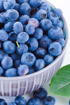 Fresh blueberries in a bowl, fruits on white