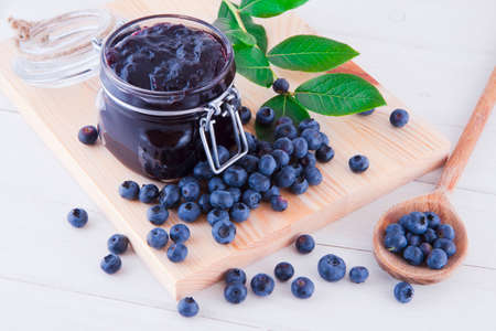 Blueberry jam and fresh fruits on the white wooden table
