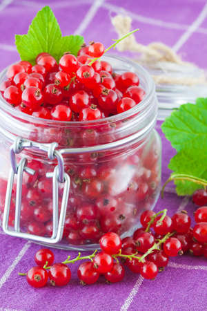Red currants in a glass jar on a kitchen table Imagens