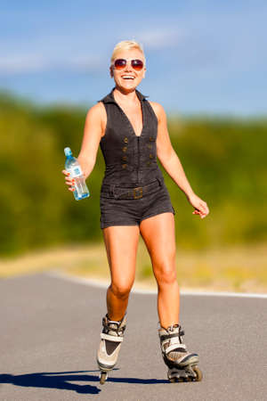 Young blonde woman rides on rollers with water drink in a bottle Imagens
