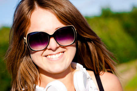 Nice young fitness girl portrait with sunglasses and earphones