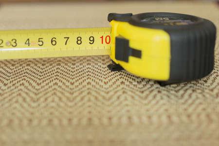 Measuring tools (samoskruchivayuschayasya tape) on a straw background.