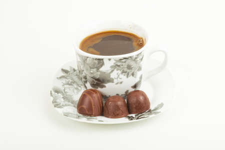 nintendo: A cup of coffee on a saucer with chocolates