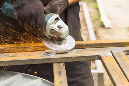 sander: Worker cleans weld manual, electric sander on stilazhe