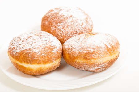 white sugar: Three donut sprinkled with powdered sugar on a plate on a white background