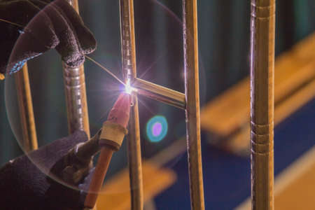 welds: Welder TIG welds fences made of polished stainless steel