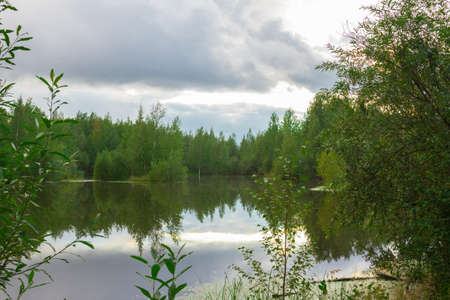 A small lake in a wooded area next to the road Stock Photo