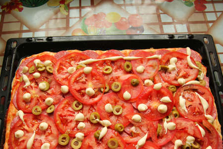 tomato slices: Pizza on a baking sheet on the kitchen table Stock Photo