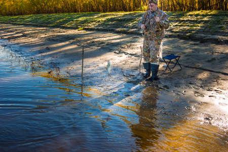 roach: Fisherman caught fishing rod on earthworm big roach Stock Photo